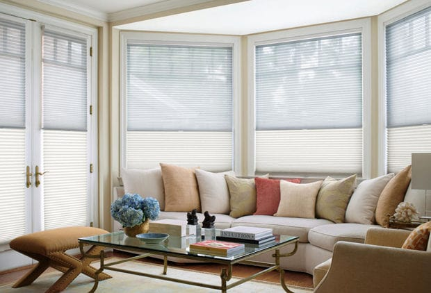 Custom cut honeycomb window shades in a living room.