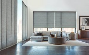 Roller shades in gray with motorized reverse rolling.