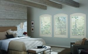 Custom cut white shutters on master bedroom windows.